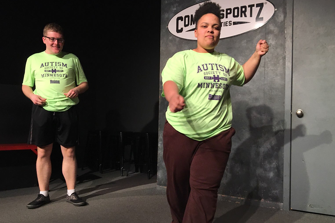 Adults on stage in front of ComedySportz sign