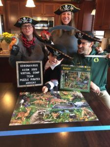Family dressed in pirate costumes with completed puzzle from 2020 puzzle competition