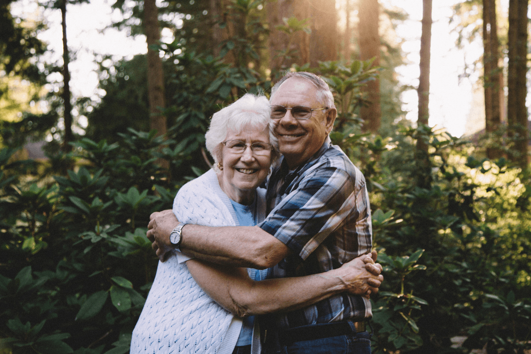 An elderly couple embraces while smiling