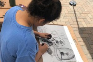 Teen female works on charcoal art drawing