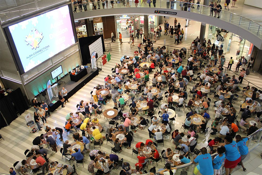 Overhead view of Mall of America rotunda; many tables of people putting together puzzles