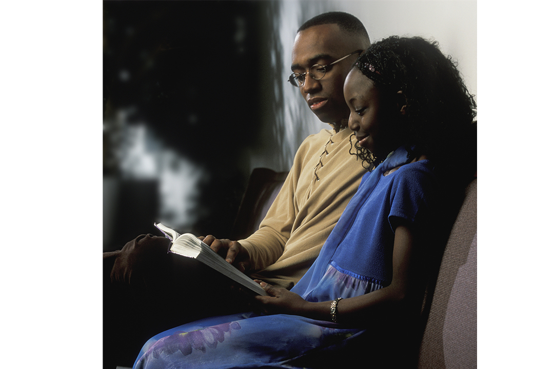 Dad reading to daughter as they sit on the couch together
