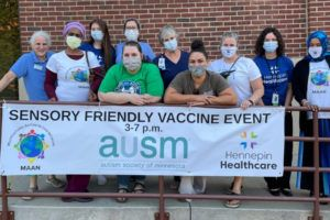 Group of people outside a brick building holding a Sensory-Friendly Vaccine Clinic banner